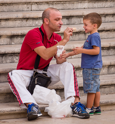 I found these stairs in a main square of a village in Sicily where there were a lot of people coming and going. I just waited for things to happen- one of which was a nice moment with this father and his son sharing some lunch. Aside from a nice moment- the man, his attire and the old stone steps let the viewer know this is in Italy