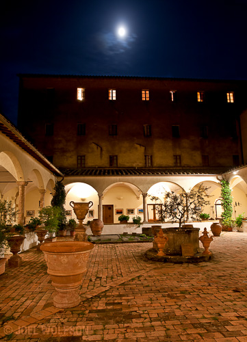This is one of my favorite places in the town where I hold my Villages of Tuscany workshop. It's a courtyard of a centuries old convent that is now a hotel. At night there are very few people and the lighting along with the moon through a misty sky adds drama to the feel of it.